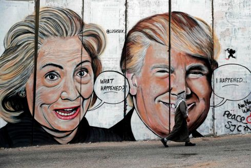 WHAT HAPPENED?: A Palestinian man walks past graffiti depicting Hillary Clinton and US president Donald Trump on the controversial Israeli separation wall separating the West Bank town of Bethlehem from Jerusalem. Photograph: Thomas Coex/AFP/Getty Images