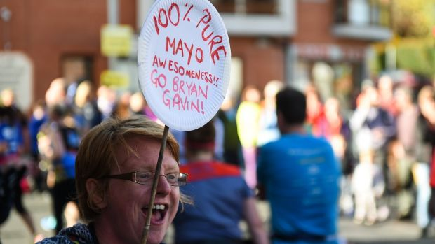A spectator shouts her encouragement as runners make their way through Chapelizod. Photograph: David Fitzgerald/Sportsfile