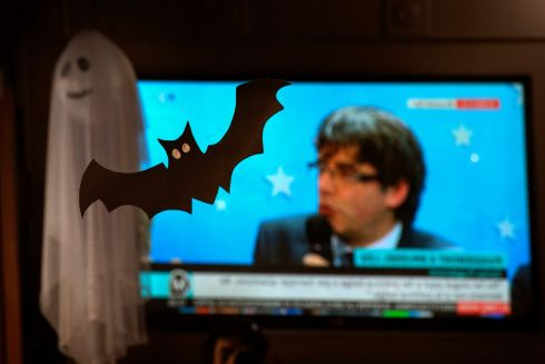 A Halloween ghost and bat decorates a bar as people watch the news conference in Brussels by ousted Catalan leader Carles Puigdemont in downtown Barcelona. Photograph: Emilio Morenatti/AP