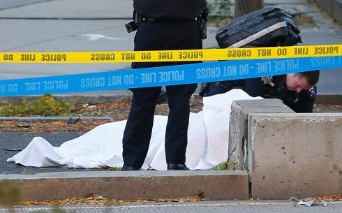 A paramedic looks at a body covered under a white sheet along the bike path  in New York.  Photo: AP/Bebeto Matthews.