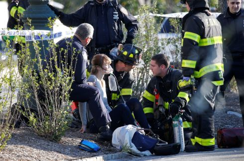 A woman is aided by first responders after sustaining injury on a bike path in lower Manhattan.  Photo: rendan McDermid