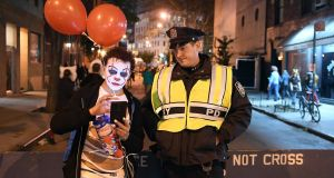 A man dressed in a clown costume talks to an NYPD officer during the 44rd Annual Halloween Parade in New York, following an attack in Manhattan that left eight people dead. Photograph: Angela Weiss/AFP/Getty Images