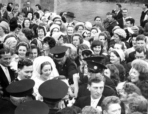 Mr. Gay Byrne and Miss Kathleen Watkins being helped through a crowd of about 300 people who surrounded the couple when they left the Church of the Nativity, Saggart, Co. Dublin, after their wedding in 1964.  Photograph: Gordon Standing / The Irish Times