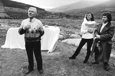 Gay Byrne, watched by the Australian-born founder of Crann, Jan Alexander, and De Danann musician, Frankie Gavin. speaking before he unveiled The Oak Glen Stone at the Oak Forest, Glencree, Co Wicklow in 1991. Photograph: Pat Langan/The Irish Times