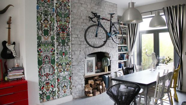 Hidden storage: Siobhan Lam's Portobello livingroom with floor-to-ceiling storage area beside chimney breast decorated with Studio Job l'Afrique wallpaper