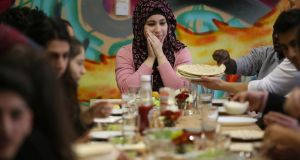 Gazal (17) a refugee from Syria, sits down to  lunch that her classmates prepared during their extra-curricular German-language programme at a Berlin school on Thursday. Photograph:  Sean Gallup/Getty Images