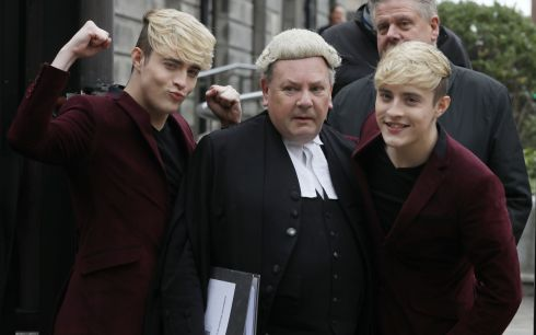 BEFORE THE JUDGES: John and Edward Grimes, better known as Jedward, with their barrister, Desmond Murphy at the Four Courts after the settlement of a High Court action taken against them by Patrick Joseph Noonan over an alleged merchandising agreement. Photograph: Collins courts