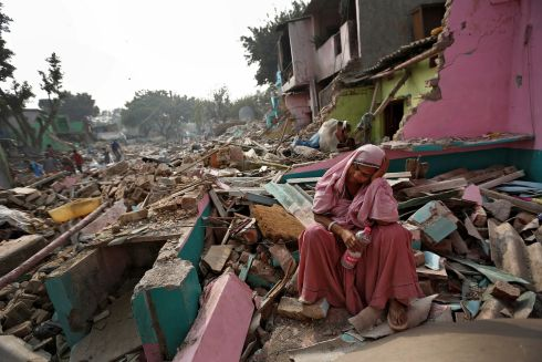 BROKEN HOME: A woman amid the rubble of her home in a slum which was razed to the ground by local authorities in a bid to relocate the residents, Delhi, India. Photograph: Cathal McNaughton/Reuters