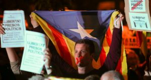 A man holds an Estelada (Catalan separatist flag) during a gathering in support of the jailed members of the dismissed Catalan cabinet in  Barcelona on Thursday night. Photograph: Albert Gea/Reuters