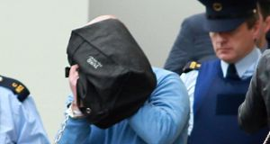 Michael Murray (in blue jumper, hiding behind black bag) whose sentence for the rape and sexual assault of a woman whose child he abducted in the same incident was increased to 19 years following an appeal by the DPP. File photograph: Courts Collins
