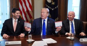 "US President Donald Trump speaks while holding up ""Simple, Fair, 'Postcard' Tax Filing"" cards as US house speaker Paul Ryan, a Republican from Wisconsin (left) and Representative Kevin Brady, a Republican from Texas and chairman of the house ways and means committee, react during a meeting in the Cabinet Room of the White House in Washington. Photograph: Olivier Douliery / Bloomberg"