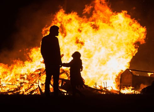 FANS OF THE FLAMES: A father and daughter watch a Halloween bonfire in Tallaght on Tuesday night. Photograph: Dave Meehan