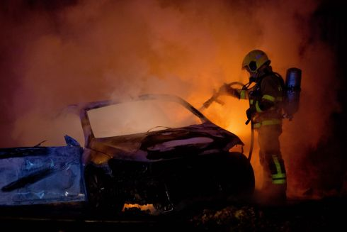 DOUSING THE FLAMES: A firefighter tackles a car fire in Walkinstown, in Dublin, in the run-up to Halloween. Photograph: Tom Honan