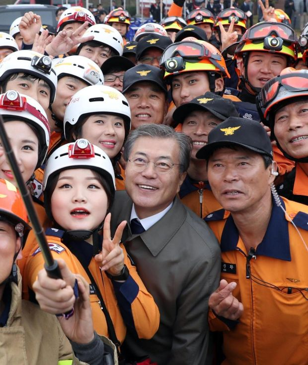 South Korean president Moon Jae-in poses for a selfie with firefighters at an event to celebrate Firefighters Day in Cheonan, South Korea, on Friday. Photograph: Yonhap/EPA