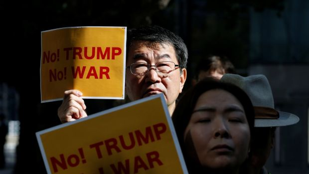 Protesters hold placards during a rally against US president Donald Trump's visit to Japan, near the US Embassy in Tokyo on Friday. Photograph: Toru Hanai/Reuters