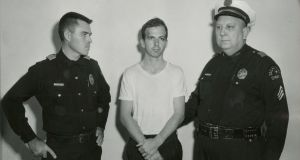 Lee Harvey Oswald with Dallas police officers in  November 1963. Photograph:  Dallas police department/Reuters