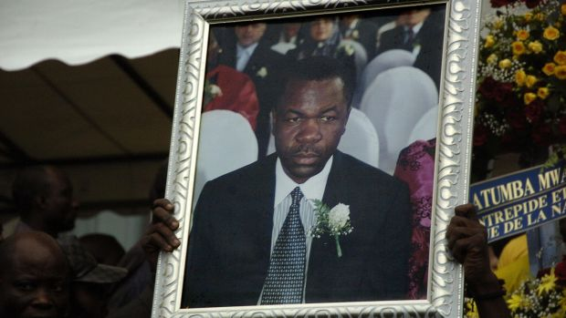 A man holds up a photograph of Augustin Katumba Mwanke, a close aide of President Joseph Kabila, who was killed in a plane crash on February 12th, 2012, during a ceremony at the People Palace in Lingwala, Democratic Republic of Congo. File photograph: Junior D Kannah/AFP/Getty Images