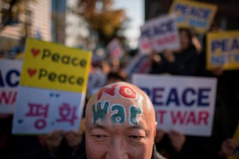 PEACE PROTEST: Demonstrators hold placards during a peace rally in Seoul. Thousands of South Koreans called for peace in a protest against an upcoming visit by US president Donald Trump as he begins a tour of Asia. Photograph: Ed Jones/AFP/Getty Images
