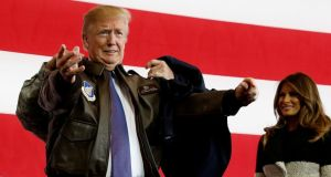 """Greatest threat"": a soldier helps Donald Trump put on a flight jacket for his speech to US troops in Japan. Photograph: Jonathan Ernst/Reuters"