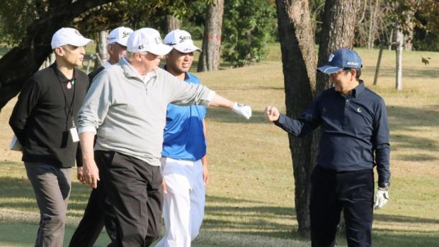Fist bumps: Donald Trump and Japanese prime minister Shinzo Abe (with Hideki Matsuyama, second right) on the golf course. Photograph: Japanese government via Jiji Press/AFP/Getty