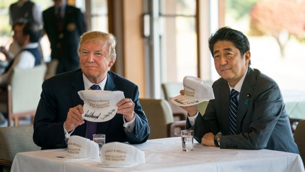 """Donald & Shinzo Make Alliance Even Greater"": Donald Trump and Shinzo Abe with golf hats they signed. Photograph: Doug Mills/New York Times"