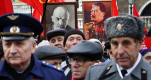 Russian communists carry Soviet red flags and portraits of  Vladimir Lenin and Josef Stalin at a ceremony at Red Square in Moscow. Photograph: Yuri Kochetkov