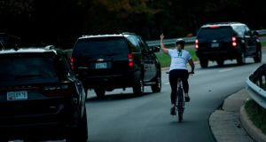 Juli Briskman gestures with her middle finger as a motorcade with US President Donald Trump departs Trump National Golf Course in Sterling, Virginia. Photograph:  Brendan Smialowski/AFP/Getty Images