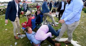 Two men fall onto the ground as they have a fight after the running of the 157th version of the Melbourne Cup at Flemington racecourse in Melbourne. Photograph: Reuters
