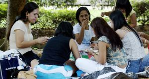 Domestic helpers enjoy a picnic in the shade at 'Gulung-gulung' park in Singapore, in 2003.  Photograph:   Roslan Rahman/AFP/Getty Images