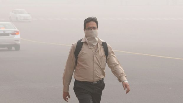 An Inidan man with his face covered walks at Rajpath Avenue engulfed in smog near the Indian president's house, in New Delhi. Photograph: EPA