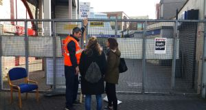 A striking worker speaks with tourists at a locked-up Tara Street Dart Station in Dublin  during the rail strike. Photograph: Frank Miller/The Irish Times