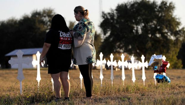 Sonia Yanez and Laura Torres visit a line of crosses before a vigil for the victims of Sunday's First Baptist Church shooting, in Sutherland Springs, Texas. Photograph: David J Phillip/AP Photo