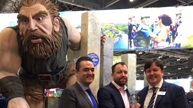 David Wood and Cormac Ó Suilleabháin, both from Tourism Ireland, accept the award for 'best stand feature' from Jonathan Hull from World Travel Market (right) as giant Finn McCool looks on. Photograph: Tourism Ireland