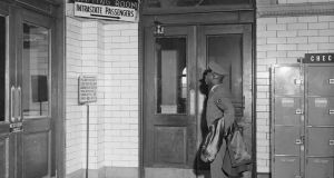 Airman Second Class Philip Wagner, of New York City pauses to examine the new appendage to the 'Coloured'waiting room sign in Atlanta's Terminal Station in 1956.