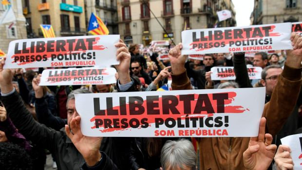 People hold placards reading 'Free political prisoners' during a demonstration outside the Generalitat Palace in Barcelona Wednesday during a regionwide strike called by a pro-independence union. Photograph: Gabriel Bouys/AFP/Getty Images