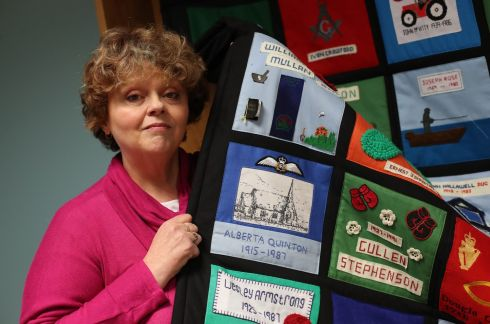 Aileen Quinton, whose mother Alberta Quinton was murdered in the Enniskillen bombing, holds a quilt she helped make as a memorial.  Photograph: Niall carson / PA