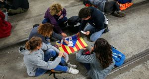 Protesters play cards on top of a Catalan separatist flag while blocking the tracks inside the station of the high speed train AVE during a partial regional strike in Girona, Spain. Photograph: Albert Gea/Reuters