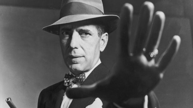 1951: American actor Humphrey Bogart carrying a gun and holding out his hand, in a still from director Bretaigne Windust's film, 'The Enforcer'. Photograph: American Stock/Getty Images