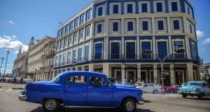 A car passes by the Telegrafo Hotel in Havana on Wednesday. Tighter restrictions on US travellers to Cuba will go into effect on Thursday, the White House  said. Photograph: Yamil Lagey/AFP/Getty Images