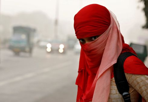 NEW DELHI SMOG: A woman wearing a scarf to protect herself waits for a passenger bus on a smoggy morning in New Delhi, India. Schools stayed shut and people were instructed to stay indoors due to the dangers of breathing in smog particles. Photograph: Saumya Khandelwal/Reuters