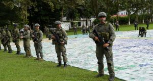 Colombian police and soldiers guard more than 12 tons of seized cocaine in Apartado in Colombia. Photograph:  Colombian presidency via Reuters.