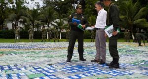 Colombian president Juan Manuel Santos speaks to police in the middle of packages containing cocaine valued at an estimated $360 million  in Apartado,  Antioquia, Colombia. Photograph: Efrain Herrera/EPA.