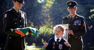 Mary Hannon (10), Celbridge, Co Kildare, wearing her great-grandfather's Old IRA service medal, with Lieut Stephen Cunningham, and Sgt Amy Hopkins, at a Defence Forces ceremony, to commemorate the centenary of the 1916 Rising , at St Raphael's Special School, Celbridge. Photograph: Eric Luke / The Irish Times