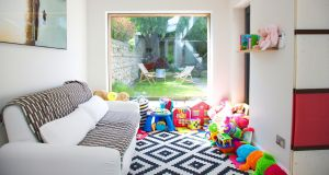 A playroom has replaced the dining space, and is furnished with a robust Ikea sofa.