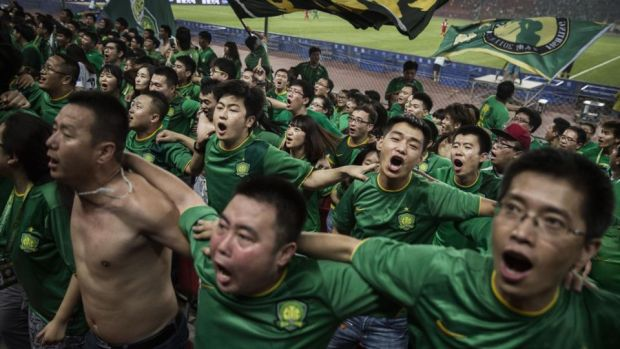 Beijing Guoan: ultra supporters celebrate a goal against Chongcing Lifan in the Chinese Super League. Photograph: Kevin Frayer/Getty