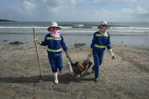 Cleaners gather debris on the beach in the central Vietnamese city of Danang. Photograph: Getty Images