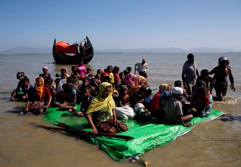 Rohingya refugees wait for permission from a Bangladesh  guard to continue after crossing the Bangladesh-Myanmar border. Photograph: Navesh Chitrakar/Reuters