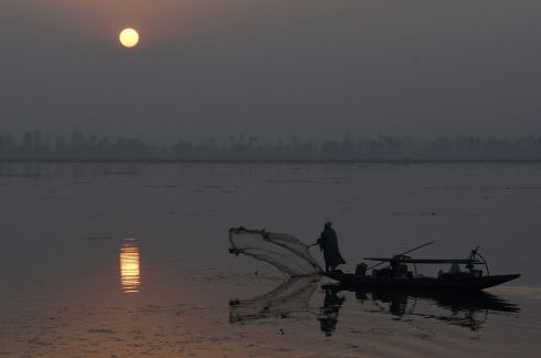 A Kashmiri fisherman casts his net from his boat during a sunset in Dal lake in Srinagar. Photograph: Getty Images