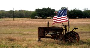 A tattered US flag flies on an old tractor in a farm field outside Sutherland Springs, near the site of the shooting at the First Baptist Church in Texas. Photograph: Reuters/Rick Wilking