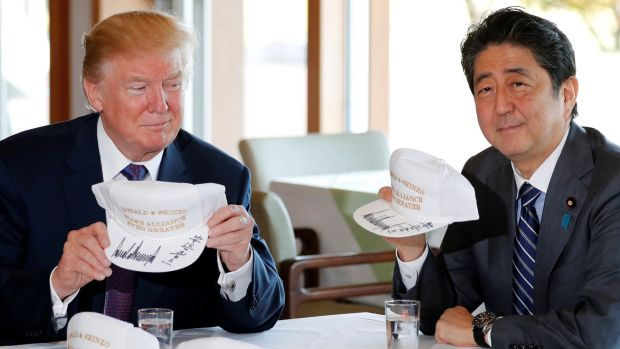 US president Donald Trump and Japan's prime minister Shinzo Abe hold hats they signed, reading 'Donald & Shinzo Make Alliance Even Greater' before lunch and a round of golf in Kawagoe, Japan. Photograph: Reuters/Jonathan Ernst